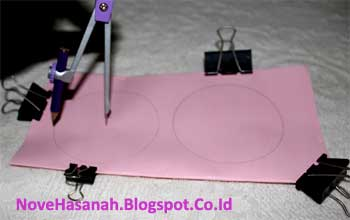 dengan menggunakan jangka kita membuat dua buah gambar lingkaran berdiameter sekitar 6 cm untuk nantinya digunting sehingga terbentuk helaian-helaian lingkaran yang merupakan bentuk dasar hiasan dekoratif untuk penghias kelas ini