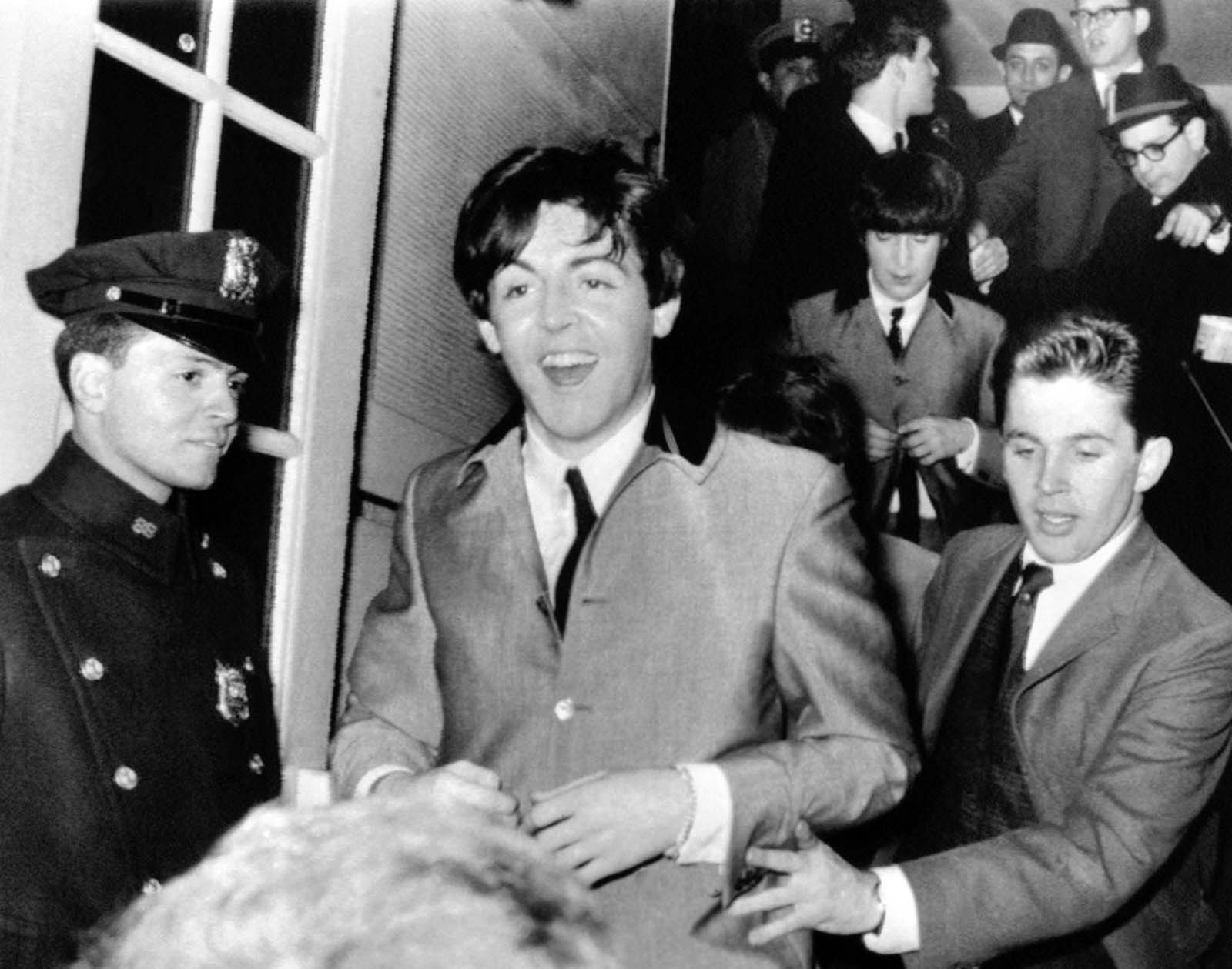 Beatle Paul McCartney flashes a smile as he rushes from New York's Carnegie Hall after two wild performances on February 12, 1964. Behind him is band mate John Lennon.