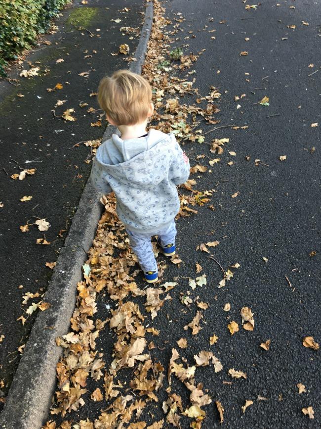 toddler-kicking-autumn-leaves
