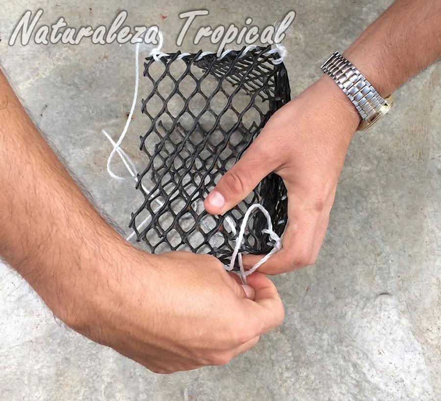 Utilizar los fragmentos de cuerda para unir los bordes de la maceta; esto lo podemos hacer entrelazando el cordel por los bordes de la maceta de manera que el tejido mantenga los bordes unidos. Los cordeles deben unir dos bordes diagonales, es decir, unir en forma de X.