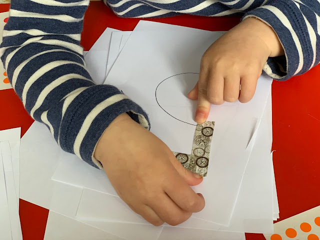 A toddler Sticking washi tape on the straight line parts of the number 5