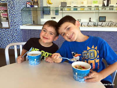 Jackson and Andrew pausing while eating fro yo to smile for mom