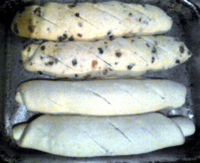 Cuatro panes de queso en asadera, sin hornear. Dos de ellos con chicharrones.