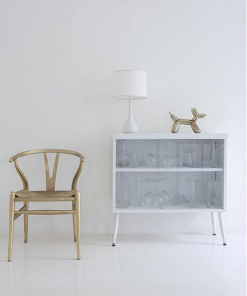 Zimmer mit weißer Wand und weißem Boden und einem gold lackierte Wishbone Chair