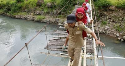 Pak guru menggendong muridnya menyebrangi jembatan