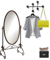 Abril | 30 peças x 30 dias: Espelho de pé, cabide com blazer de riscas preto e branco e mala amarela pendurados, caixa preta com sabrinas padrão cobre em cima.