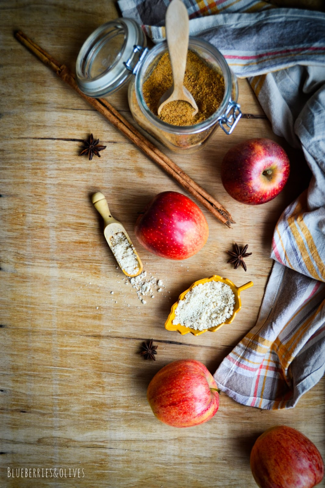 Ingredientes galletas caseras manzana y coco, harina, ramas canela, azúcar de coco, anís estrellado, manzanas rojas sobre madera antigua, trapo de cocina