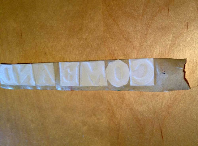 iron-on letters cut out and attached to masking tape