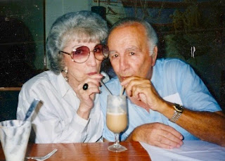 my grandparents sitting side by side, sipping the same milkshake from separate straws, adorably