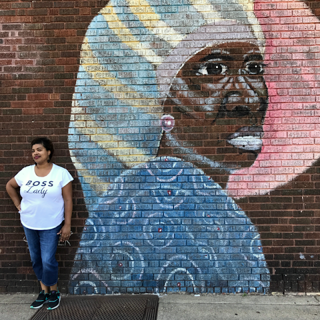 a black woman standing next to a mural