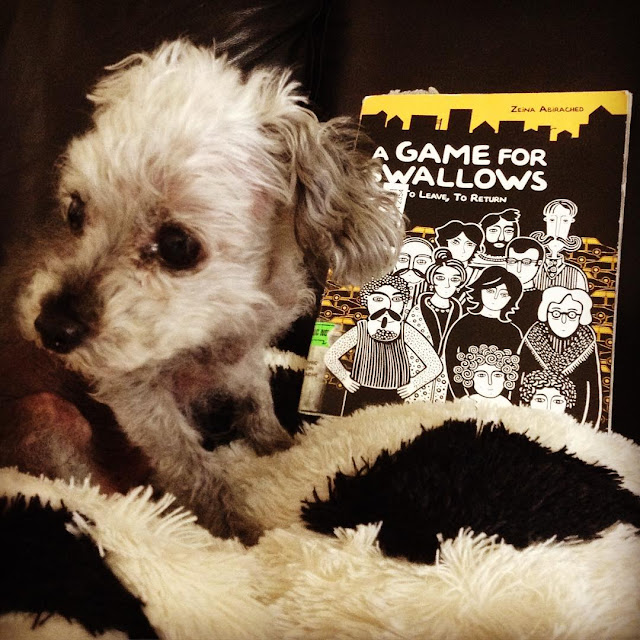 Murchie hunches down and looks away from a trade paperback copy of A Game For Swallows. The book's cover features a black and white illustration of many adults of multiple genders gathered behind two small, curly-haired children. Everyone looks very serious.