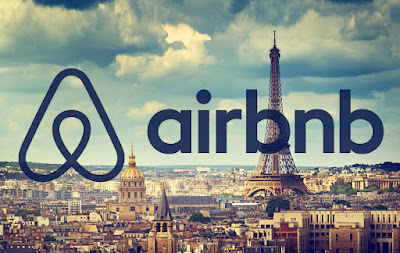 Logo Airbnb na tle Paryża