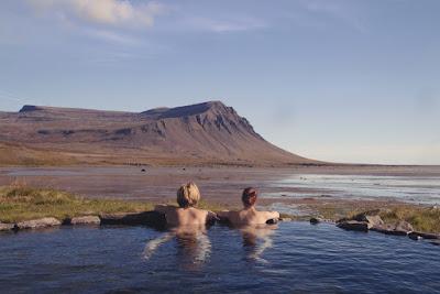 Pareja de visitantes dentro de las aguas termales un plan muy romántico que puedes hacer  Islandia
