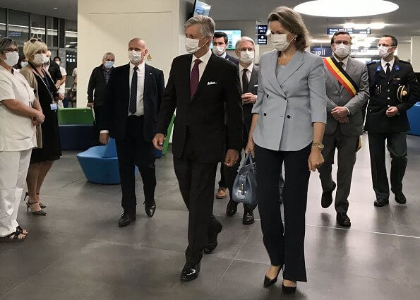 Queen Mathilde wore a blue double-breasted blazer by Emporio Armani. Queen carries Armani bag. Meghan Markle