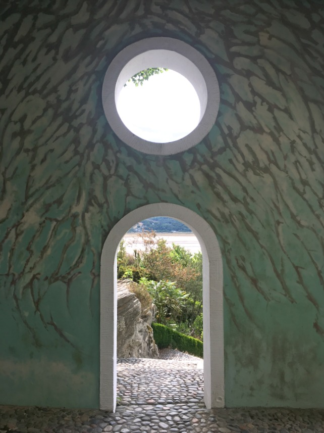 Portmeirion-Wales-View-through-arch-and-round-window-with-painted-wall