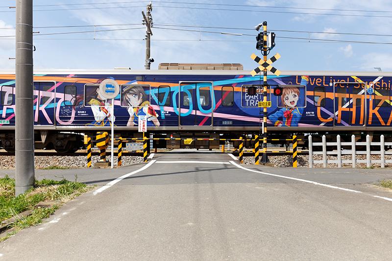 伊豆箱根鉄道駿豆線「HAPPY PARTY TRAIN」ラッピング電車。伊豆長岡と韮山間の踏み切りにて。