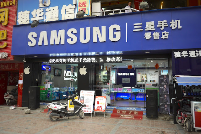 store with large Samsung sign displaying Nokia and Apple products