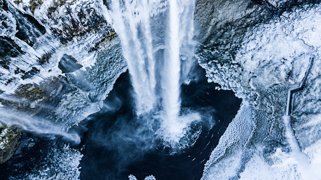 Aerial view of icy and snowy Seljalandsfoss waterfall during 5-day Iceland winter itinerary