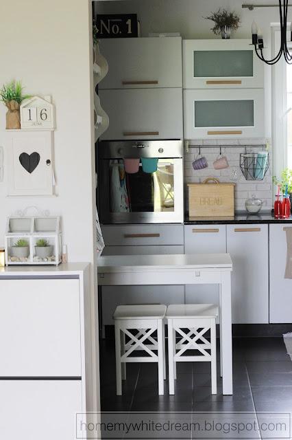 Drewniany chlebak, biała kuchnia, biały salon, biały stół, biały stół i krzesła, białe drewniane meble, drewniane uchwyty do mebli w kuchni,