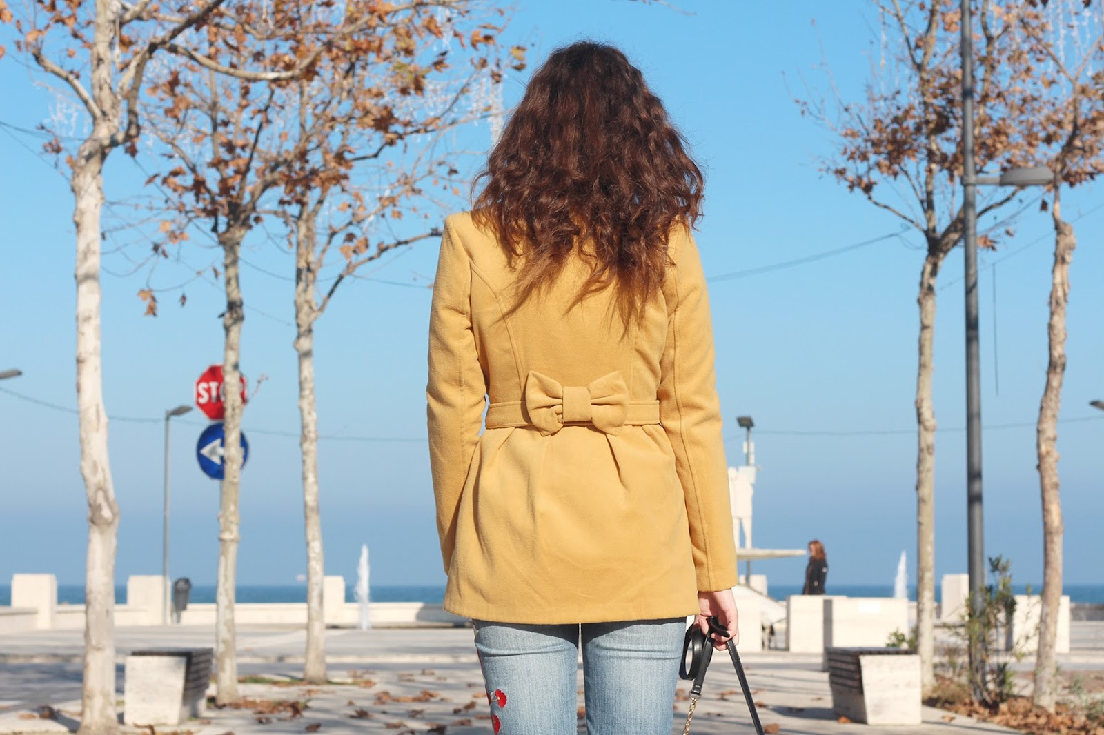 fashion blogger italy italia trend style vogue outfit ootd look flave pants denim jeans pantaloni zampa janeston necklace collana camera bag accessorize borsa reflex mustard coat bow cappotto giallo fiocco
