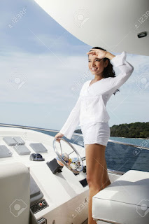 escort girl standing at controls of yacht