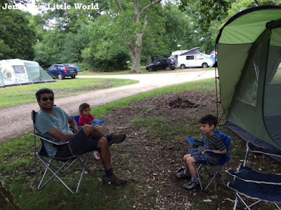 Family sitting outside tent