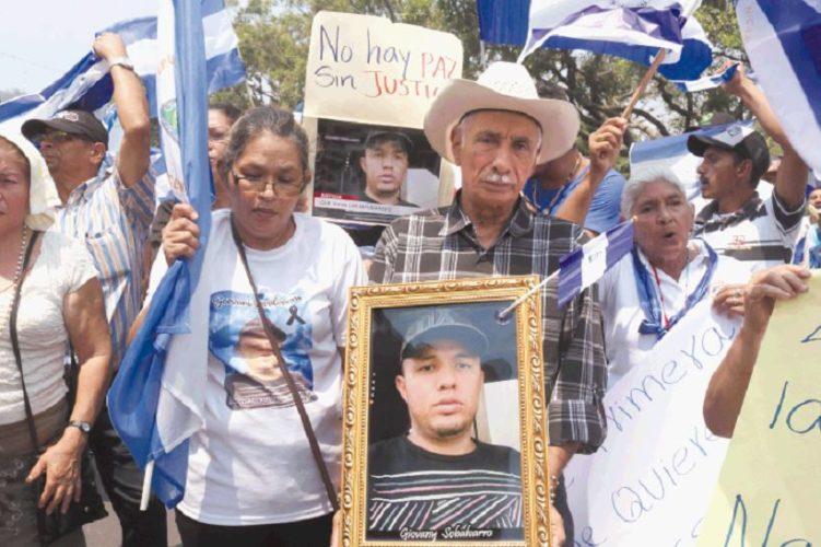 Familiares alzan el retrato de Giovanny Sobalvarro, uno de los 60 jóvenes muertos y desaparecidos / HOY