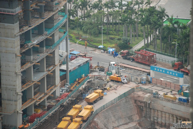 Photo of yellow trucks waiting down on the street by the building under construction