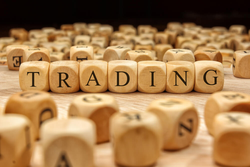 The word trading in wood blocks surrounded by other lettered wood blocks