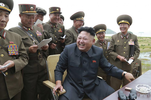 Photos of the Dear Leader controlled by Korean Central News Agency. Military leaders surround a laughing Kim Jong-un seated at a table outdoors, watching the test firing of an ultra precise rocket, 2014. Mutual Assured Lunacy, postscript and Other stories of Trump and Megalomaniacs. marchmatron.com