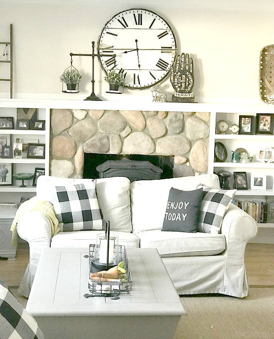 Neutral farmhouse living room with love seat and mantel with clock