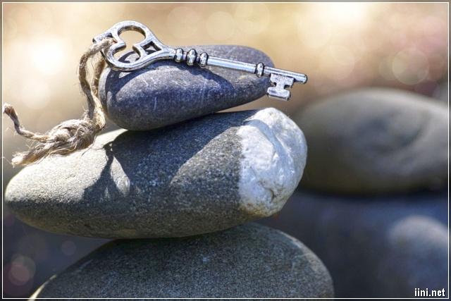 ảnh chìa khóa hình trái tim đặt trên những hòn đá