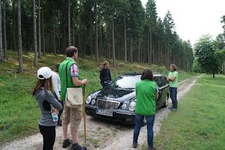 Mehrere Personren stehen um ein Auto herum und unterhalten sich. Der Wagen und die Personen stehen auf einem Waldweg.
