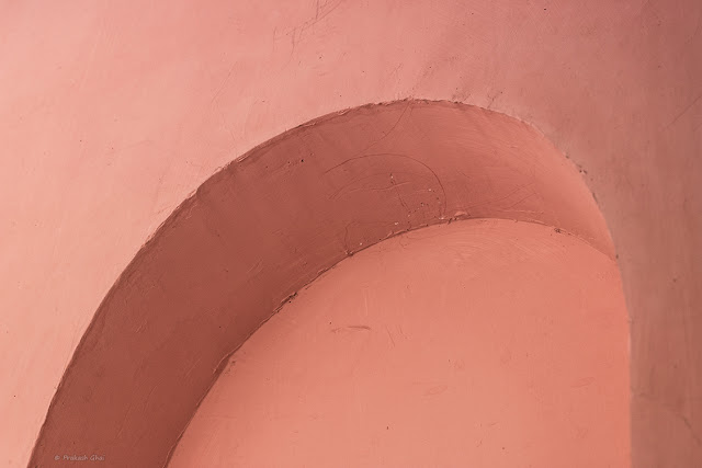 A Minimalist Photo of a Pink Curve on a Pink wall.