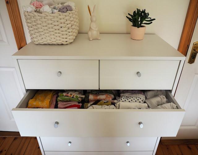 valkoinen lipasto, keramiikkapupu, vauvan vaatteita, harsoja