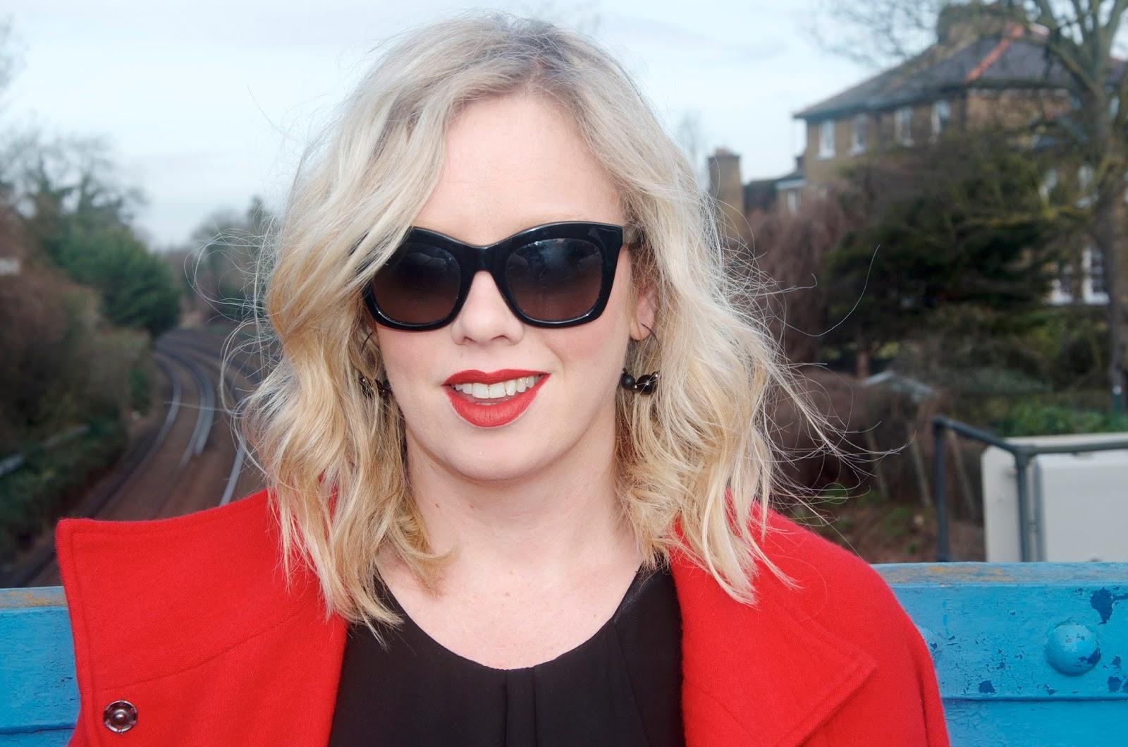 black beaded hoop earrings and black wayfarer sunglasses