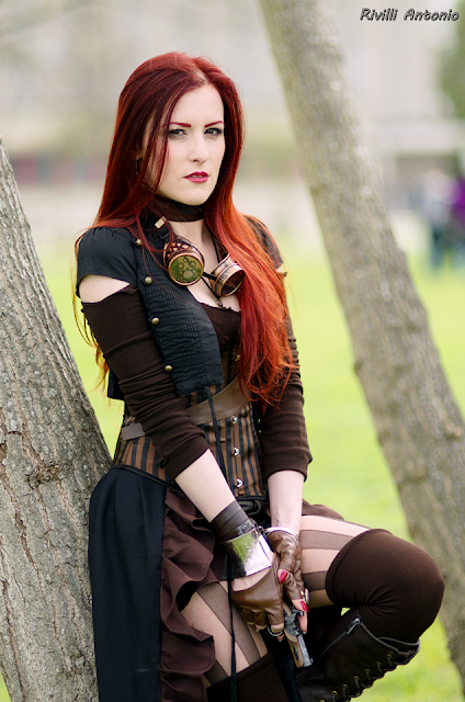 Steampunk woman with red hair dressed as a huntress, carrying a gun, wearing striped stockings, corset, shorts, and skirt. Women's steampunk fashion.