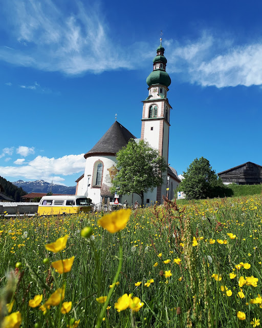 Volkswagen T2 bus in front of a church in the Wildschönau valley in Tirol, Austria