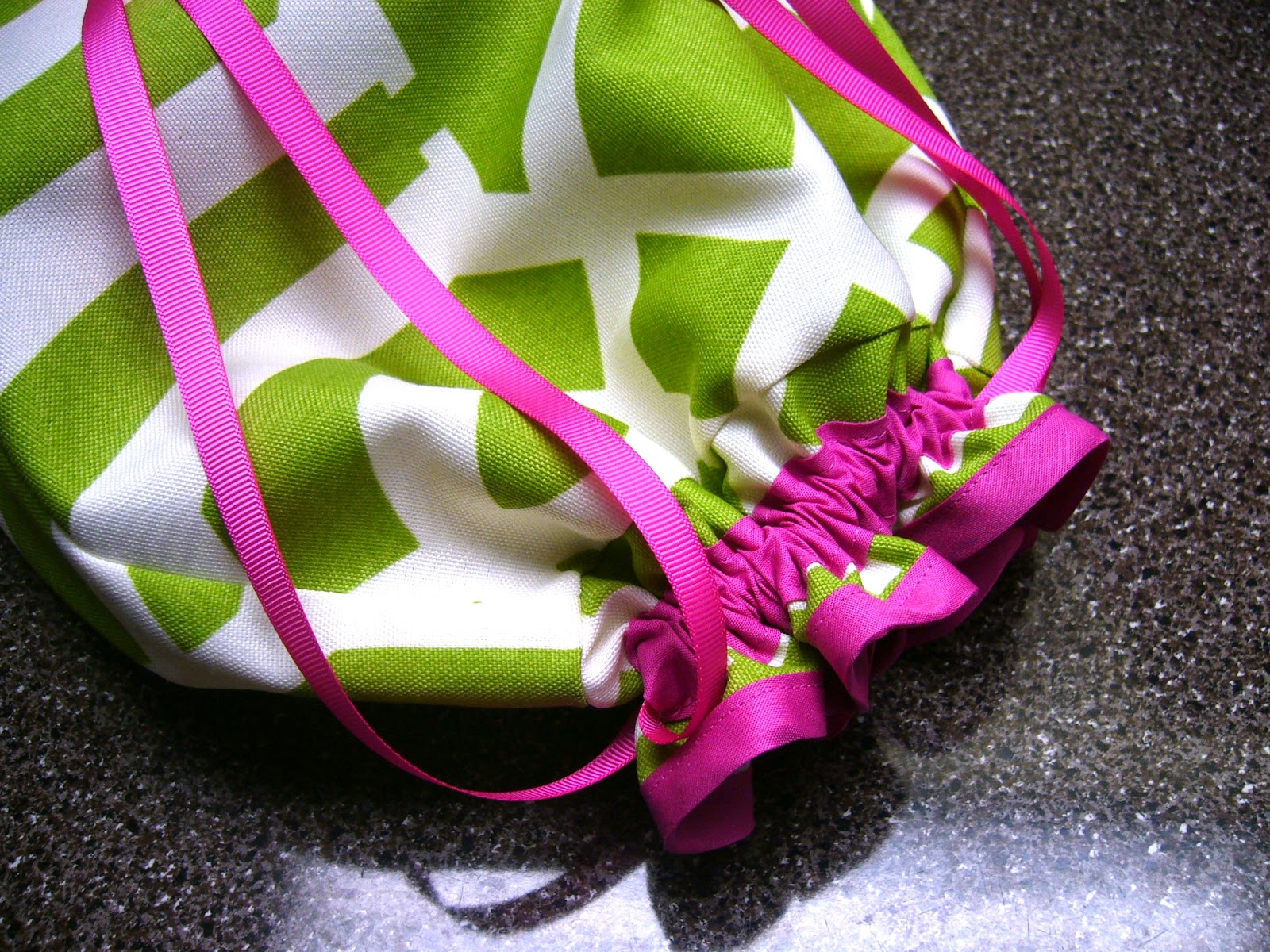 Green and pink drawstring bag for OCC shoe box gift.