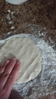presing the dough ball to make it flatten as a tortilla