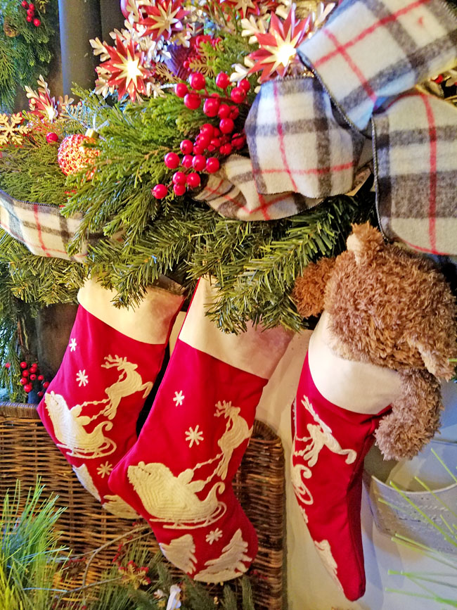 red and white Christmas stockings on mantel with green garland