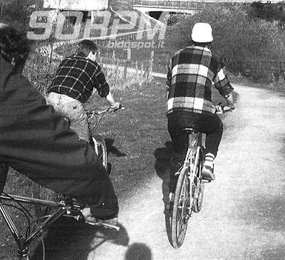 Un gruppo di amici percorre strade di campagna in sella a mountain bike degli anni '80.