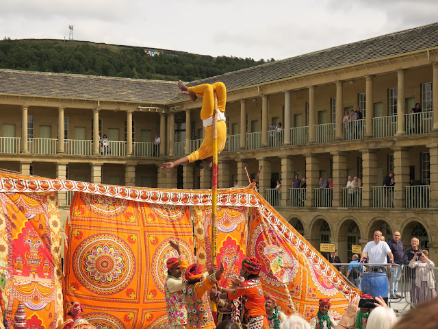 Man in yellow upside down on Pole. Circus Raj at Piece Hall in Halifax UK.