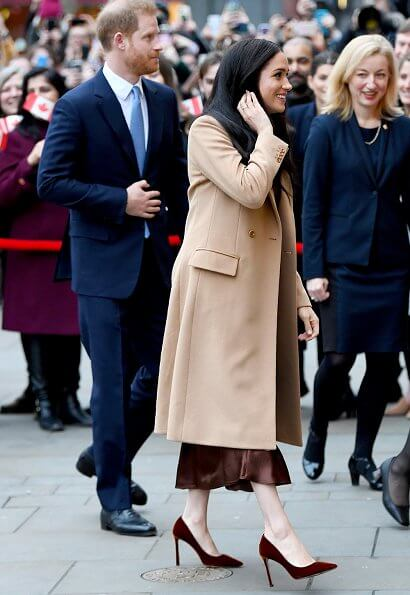 Meghan Markle wore Stella Mccartney double-breasted wool coat and Massimo Dutti brown satin midi skirt. Prince Harry