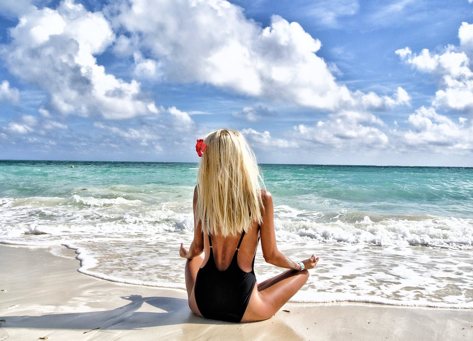 slim woman at the beach sitting in the ocean