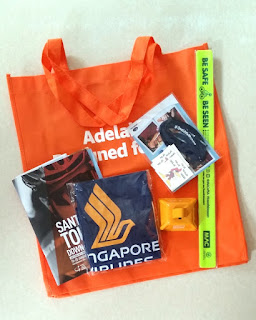 "An orange carry bag with white writing: ""Adelaide. Designed for Life."" stamped with the City of Adelaide logo and web address 'cityofadelaide.com.au/explore'. On top is a copy of the TDU 2019 program, a cowbell, reflective armband, sponsors' shoelace and backpack. 'Slip slop slap, seek, slide' temporary tattoos."