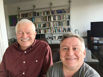 L - R Phil Friend and Simon Minty taken with a selfie stick with a bookshelf in the background.