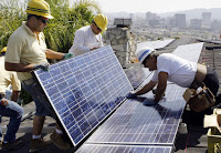 Workers install solar panels in Glendale, California. (Credit: AP/Reed Saxon) Click to Enlarge.