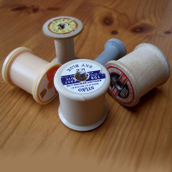 Empty sewing thread spools wooden wood plastic