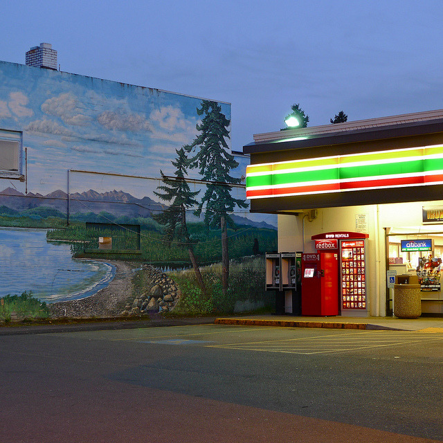 'Untitled' photographed by Steven Brooks. 7-11 at twilight. Dusk, gloaming, vacant parking lot, glowing shop lights, outdoor redbox, midwestern America. Mural of a mountain pond on the side of building.